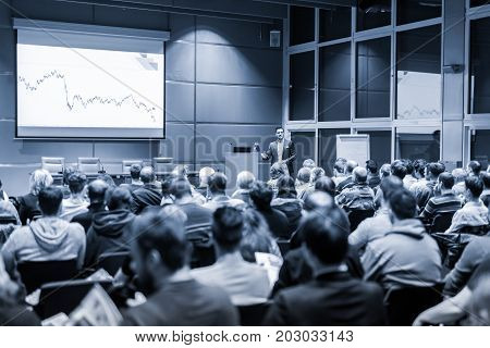 Speaker giving a talk in conference hall at business event. Audience at the conference hall. Business and Entrepreneurship concept. Black and white blue toned image.