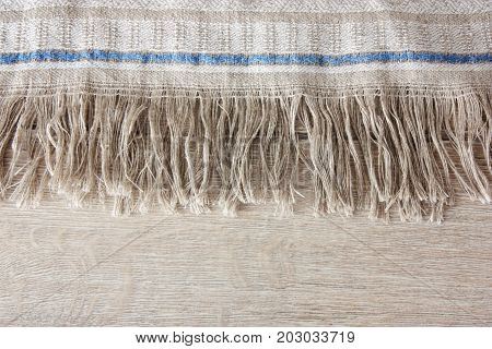 Fabric with fringe  on wooden plank .
