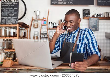 Smiling young African entrepreneur standing at is cafe counter talking on a cellphone and reading from a notebook while using a laptop