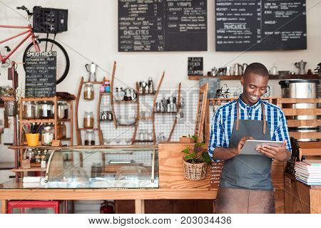 Smiling young African entrepreneur wearing an apron leaning against the counter of his trendy cafe using a digital tablet