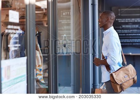 Stylish young African man carrying shopping bags and looking at a clothing store window display while out shopping in the city