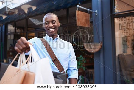 Portrait of a stylish young African man smiling and holding up shopping bags while standing in front of a store in the city