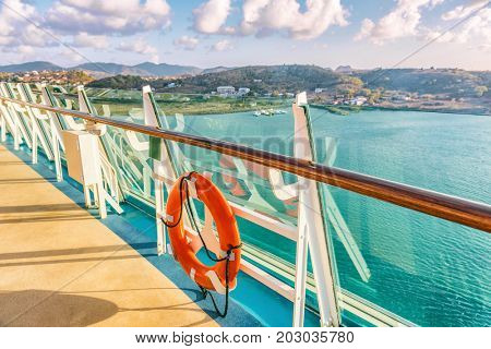 Cruise ship vacation travel Caribbean destination. View of island from boat balcony deck with railing and red lifebuoy. Tropical vacation getaway on sea.