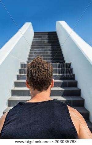 Runner going up stairs running challenge. Fitness man looking ahead at stair climbing. Staircase for cardio goal doing weight loss choice in healthy lifestyle. Man choosing difficult path. poster