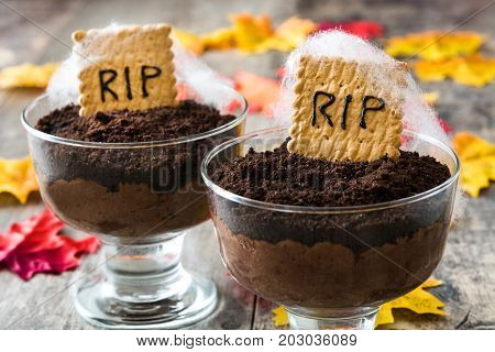 Funny Halloween chocolate mousse with tomb cookie on wooden table