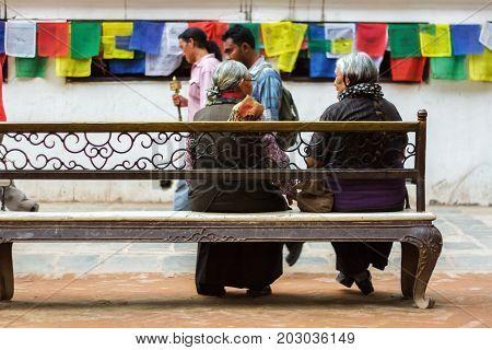 KATHMANDU NEPAL - 9/23/2015: Two elderly women sit on a bench at the Boudhanath Stupa in Kathmandu Nepal.