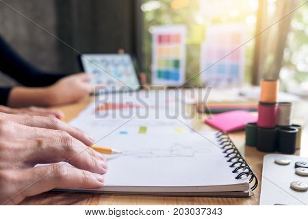 Close up of Two young dressmaker or designer colleagues's hands working as fashion designers and drawing sketches for clothes profession and job occupation Fashion Designer Stylish Concept.