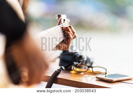 Guitarist plays guitar on wooden background close up.Music close-up. Musician with a wooden guitar
