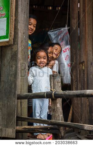SIHANOUKVILLE CAMBODIA - 7/20/2015: A group of children smile and laugh from their home in a fishing village.