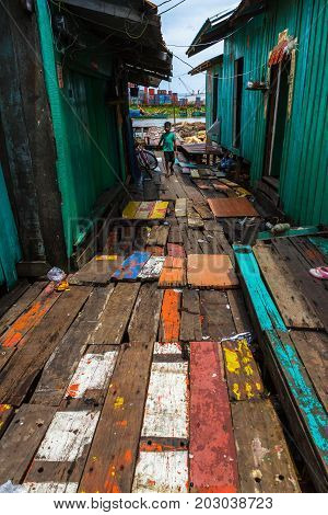 SIHANOUKVILLE CAMBODIA - 7/20/2015: A young boy walks down the colorful path in rural fishing village.