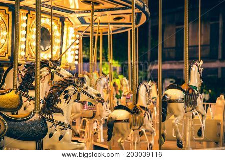 Selective focus to some part flying horse carousel carnival background with Vintage filter.