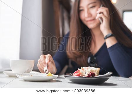 Closeup blur image of a smiley beautiful Asian woman holding and talking on smart phone with white coffee cup and dessert plates on wooden table in vintage cafe
