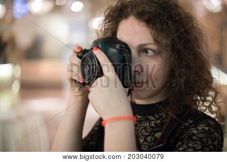 Curly woman shoots by camera indoor during event, shallow dof