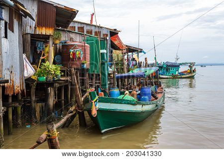 SIHANOUKVILLE CAMBODIA - 7/20/2015: A local resident sweeps her home built on stilts in a fishing village.