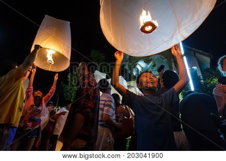 CHIANG MAI THAILAND - 12/30/2015: A boy releases a floating lantern at a temple on New Year's Eve in Chiang Mai Thailand.