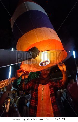 CHIANG MAI THAILAND - 12/30/2015: A male tourist releases a floating lantern at a Buddhist temple on New Year's Eve in Chiang Mai Thailand.