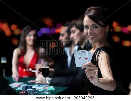 Group of an elegant people playing poker at the gambling house