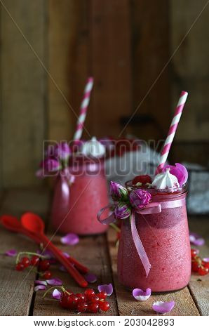 berry smoothies with red currants, strawberries, raspberries, yogurt, meringue and rose petals