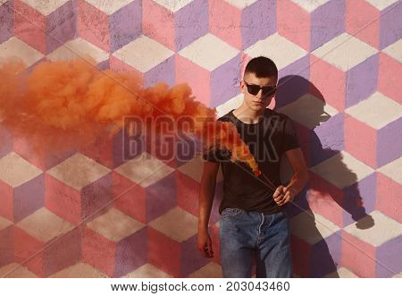 Young confident hipster in casual clothing and sunglasses looking at camera with colored smoke in hands.
