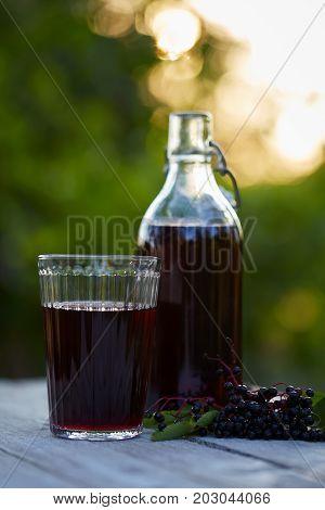 Glass Of Fresh Elderberry Syrup And Elderberries