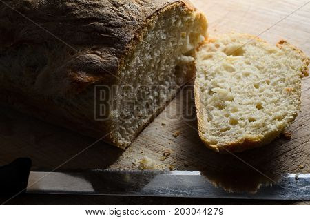 Sliced Loaf Of Fresh Bread With Knife On Wood