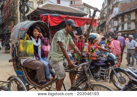 KATHMANDU NEPAL - 9/26/2015: A woman rides a ricksha taxi through the Thamel district of Kathmandu Nepal.