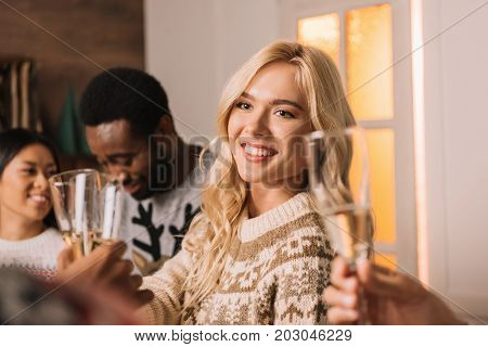 selective focus of smiling woman clinking glasses of champagne while celebrating christmas with friends