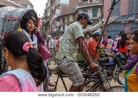 KATHMANDU NEPAL - 9/26/2015: A woman on her phone rides a ricksha taxi through the Thamel district of Kathmandu Nepal.