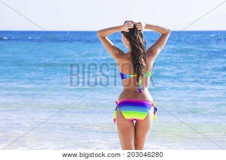 Beautiful woman in bikini walking to blue tropical sea
