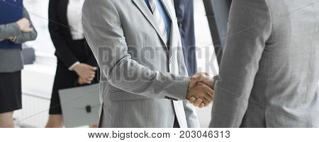 Business people shaking hands, finishing up a meeting in office