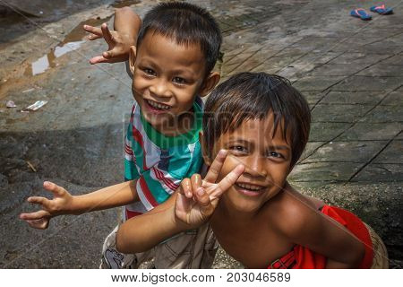 SIHANOUKVILLE CAMBODIA - 7/20/2015: Two boy play in the streets of their fishing village.