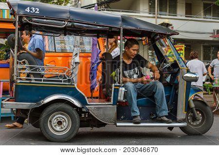 CHIANG MAI THAILAND - 6/13/2015: A tuk-tuk driver waits for customers.