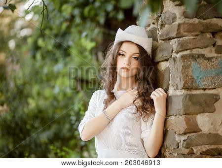 Brown-haired woman with a cocky gaze in a cowboy hat.