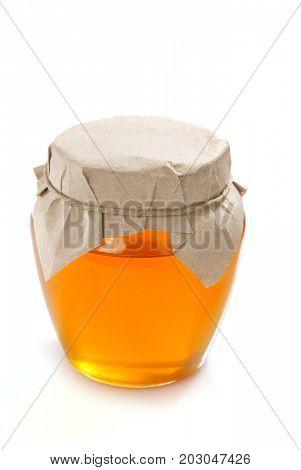 glass jar of honey isolated on white background