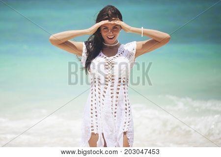 Woman in white dress posing in tropical sea beach