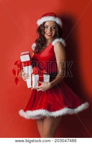 Excited surprised woman in red santa claus outfit holding Christmas presents