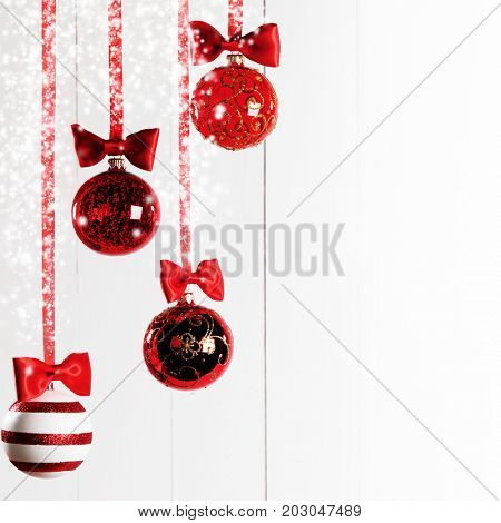 Red Christmas balls hanging on red ribbons on white background