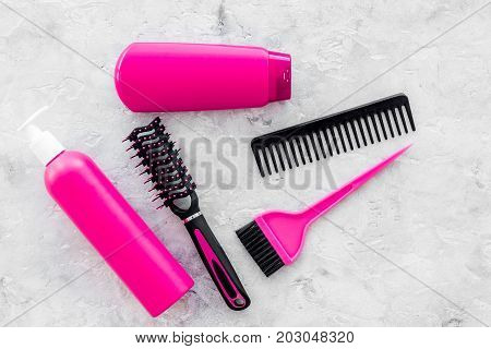 hairdresser work place with combs and brushes for styling and dyeing hair on stone desk background top view