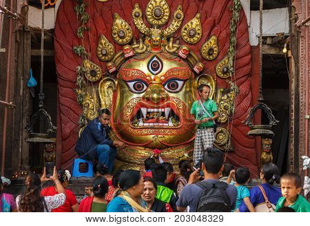 KATHMANDU NEPAL - 9/26/2015: Devotees make offerings to Bhairav at Durbar Square during the Indra Jatra festival in Kathmandu Nepal.