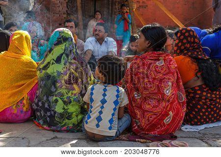 KATHMANDU NEPAL - 9/26/2015: Hindu men and women in traditional sari sit together at Durbar Square in Kathmandu Nepal.