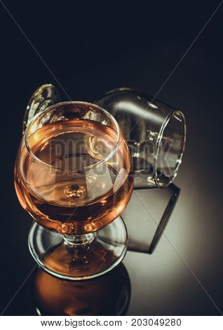 cognac glass on black glossy background