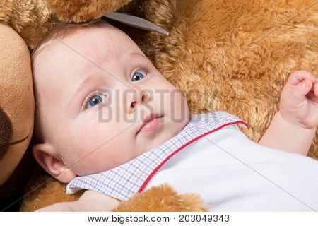 Baby Lying In Bed With A Plush Teddy Bear