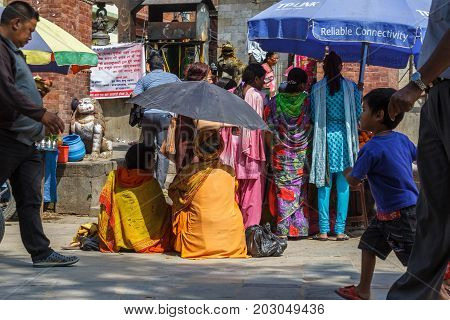 KATHMANDU NEPAL - 9/26/2015: A Sadhu uses an umbrella to block the heat during the Indra Jatra festival at Durbar Square in Kathmandu Nepal.