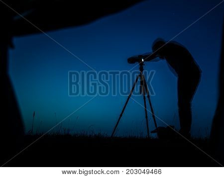 Artistic Long Exposure Photo Of A Photographer In Action. Multiple Silhouettes And A Camera Un Tripo