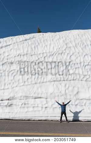 Man Smiles in Front of Tall Snow Drift