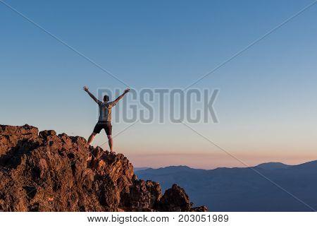 Man Stands on Rocks at Sunset on Death Valley mountain peak