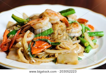 Pad Khee Mao, Stir-fried with wide rice noodles, hot peppers, carrots, green beans, onions, tomato and sweet basil leaves