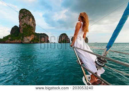 Joyful young woman portrait. Happy girl on board of sailing yacht have fun discovering islands in tropical sea on summer coastal cruise. Travel adventure yachting with kids on family vacation.