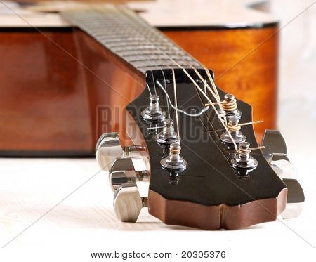Color photo of acoustic guitar tuners close-up