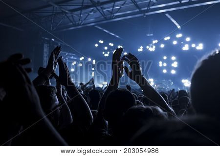 Concert goers applauding inside a music venue - selective focus